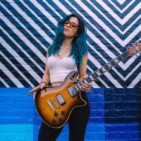 Doll-Skin-orange-guitar-slung-over-shoulder@1400x1050